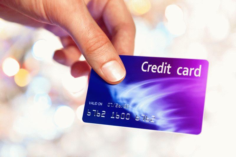 Девушка держит кредитку в руке.